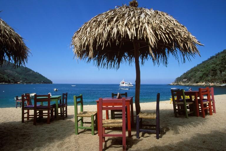 Bay and beach with wooden tables and chairs beneath thatched umbrellas, Bahia de Banderas, Playa Yelapa near Puerto Vallarta, J