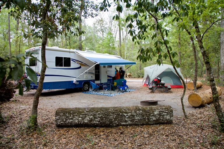 Motorhome campervan campsite with tent surrounded by logs Florida