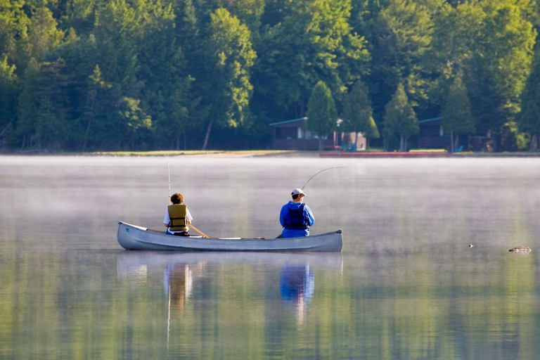 Couple fishing from canoe in New York