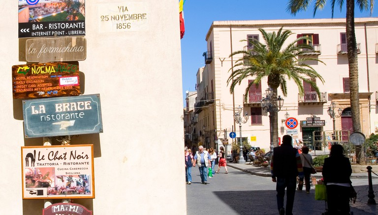 Signs on Via 25 Novembre, a busy street in the town of Cefalu on the island of Sicily, Italy