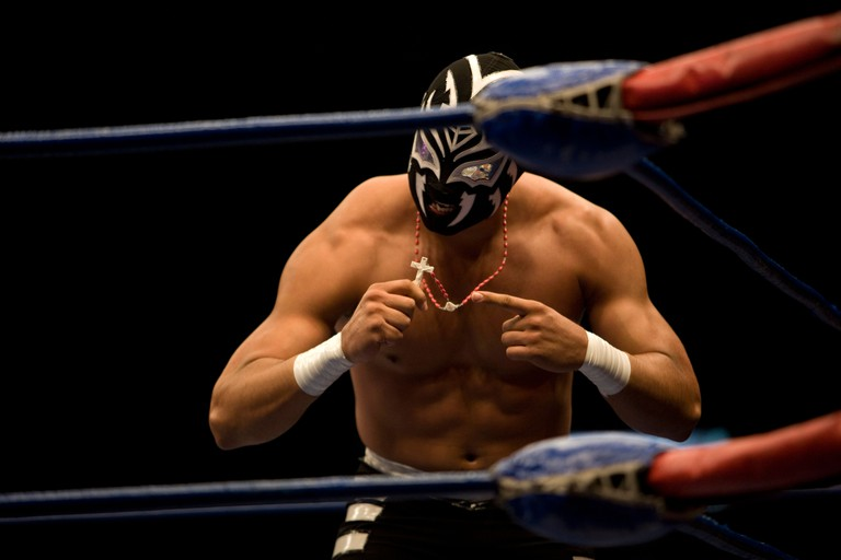 BMB47M A Lucha Libre wrestler shows the cross on his necklace as he performs in Arena Mexico, Mexico City