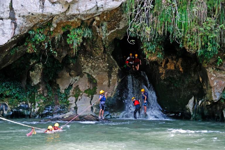 Tourists crossing Rio Claro River from a cave, Rio Claro Nature Reserve, Colombia