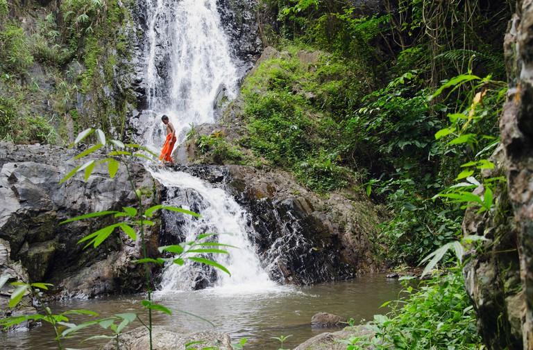 Monk walking across a waterfall, Khao Phanom Bencha National Park, Krabi, Thailand, Asia