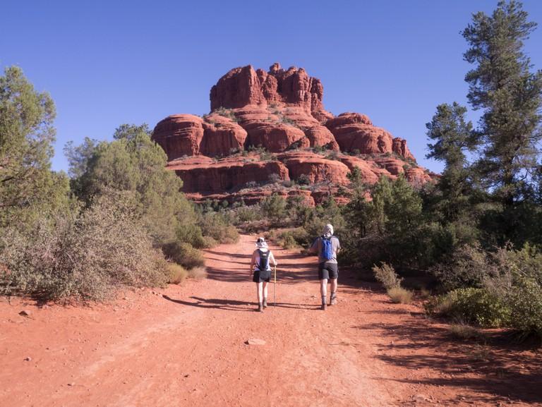2 hikers walking towards Bell Rock near to Sedona, Arizona, USA