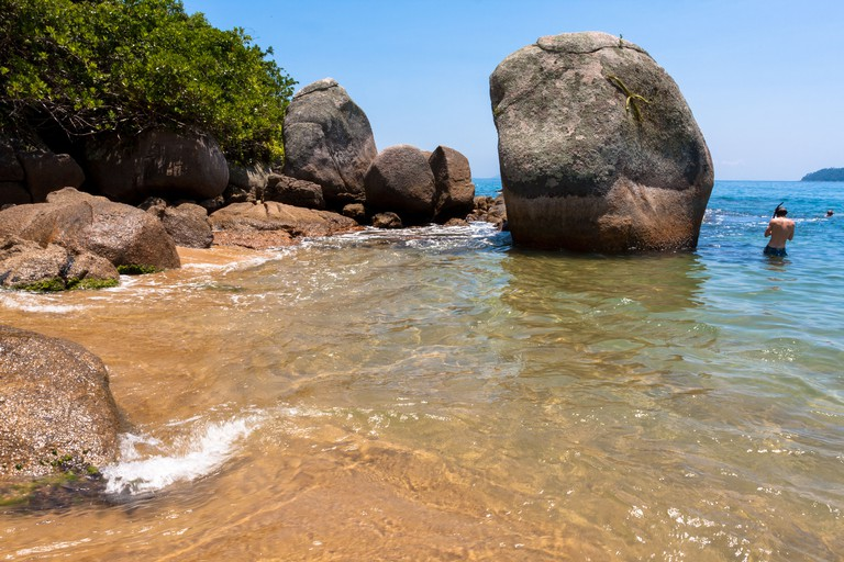 Beachgoers enjoy a gorgeous sunny day on a sandy beach at Palmas, Enseada das Palmas, Ilha Grande, Angra dos Reis, State of Rio de Janeiro, Brazil