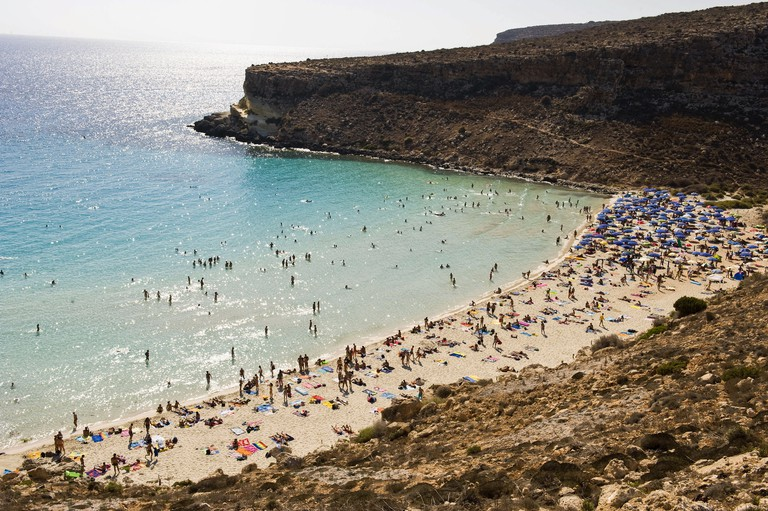 Tourists bathe in the sun on the beach of Lido Azzurro on the Southern Italian island Lampedusa, 11 August 2008. Photo: Fabrizio Villa
