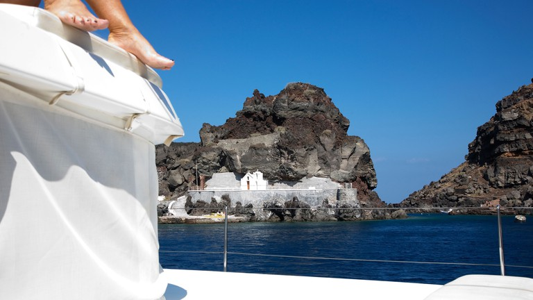 DH0M6C View of the caldera and a church from the water sailing south in Santorini