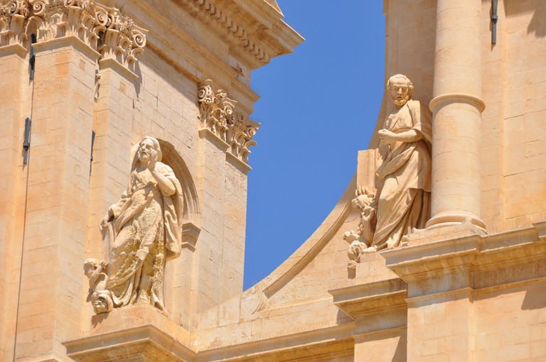 Two limestone statues on top the facade of the Noto Cathedral built in the style of the Sicilian Baroque,