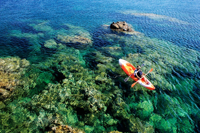 Canoeist gazes at the stunning waterscape in Greece