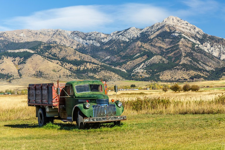 F6CJCH An old truck in a field at the foot of the Bridger mountain range in Belgrade, Montana