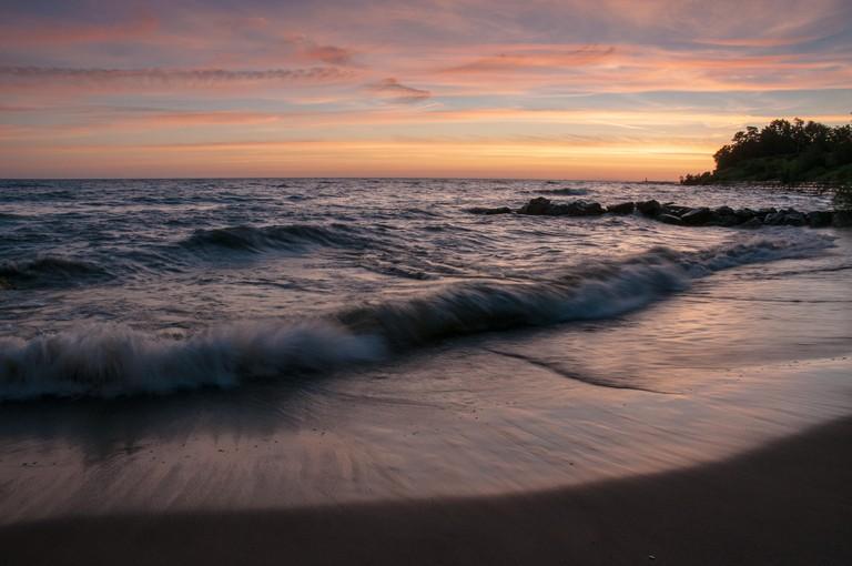 Waves crashing on Lake Erie beach at sunrise.