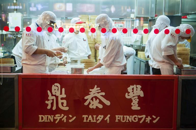 cooks prepare dumplings at the Din Tai Fung Restaurant, Beijing, China