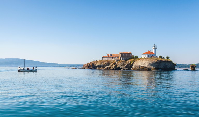 G17X9C Saint Anastasia Island in Burgas bay, Black Sea, Bulgaria. Summer coastal landscape with fishermen in wooden boat