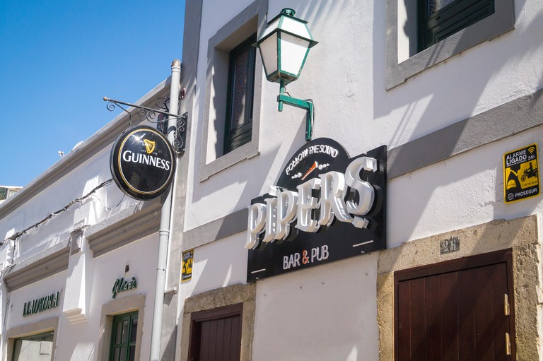 Portugal Algarve 4th c BC ancient old city port Faro Pipers bar & pub Guinness sign street light lamp on wall