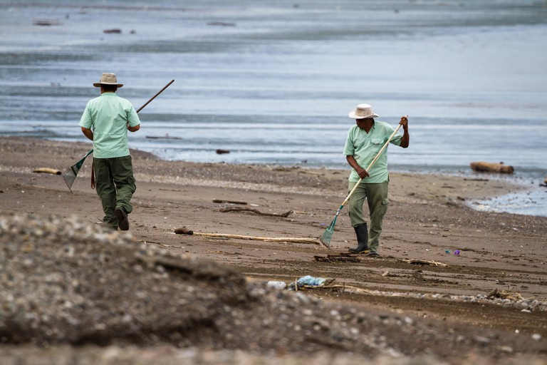 GENERIC IMAGE Tambor, Costa Rica - June 25: Hotel employees cleaning up the beach after a strom. June 25 2016, Tambor, Costa Rica.