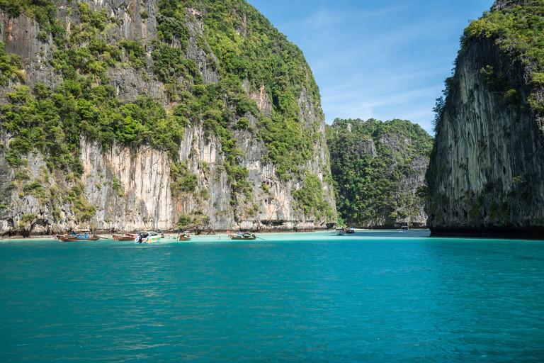 Jungle limestone cliffs around Phi-Phi Leh island with tourist boat parking