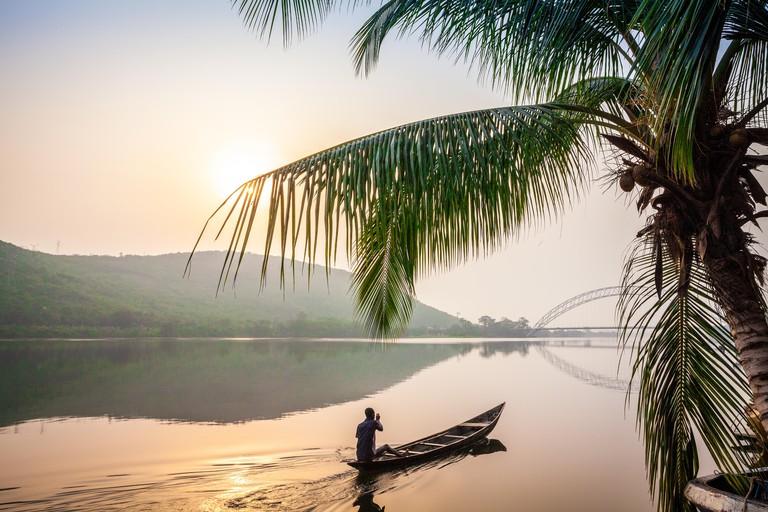 Local paddling in wooden canoe, Volta River, Ghana, Africa