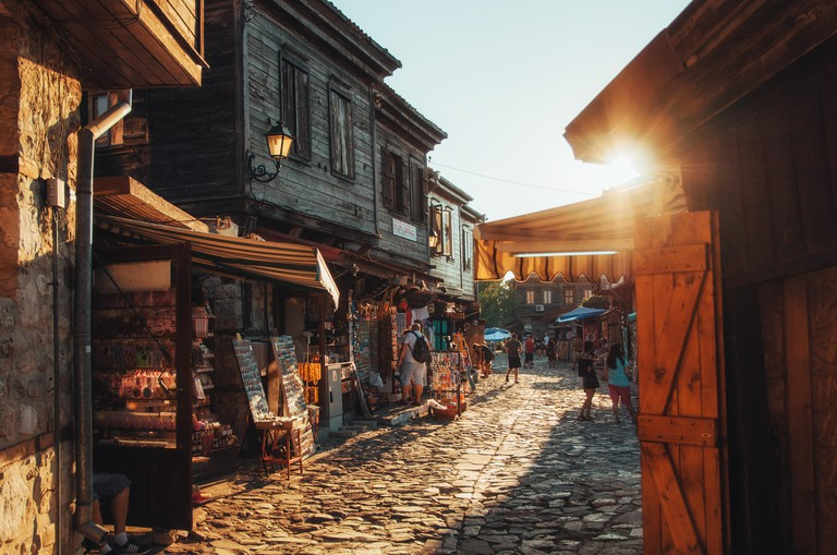 NESSEBAR, BULGARIA, AUGUST 31, 2015: People walk through streets of ancient nesebar with cafe, restaurant, shops at sunset.
