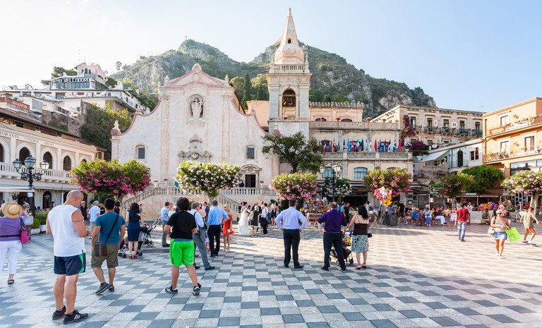 TAORMINA, ITALY - JULY 2, 2011: tourists near Church of San Giuseppe in Piazza IX Aprile in Taormina city in Sicily. The church was built between late