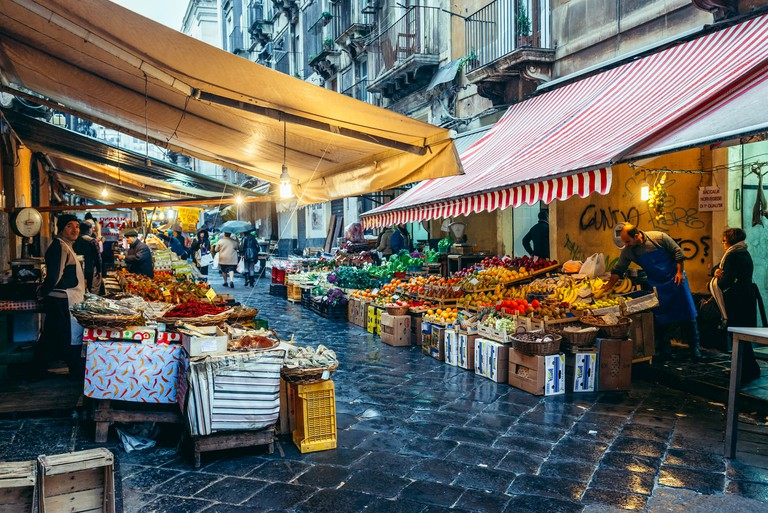 Vegetables and fruits for sale on old fish market called La Pescheria in Catania city, east of Sicily Island, Italy