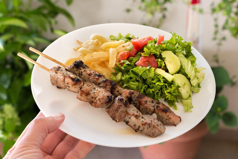 A plate of pork souvlaki with fried potatoes and green salad with tomatoes, lettuce and cucumber, home background.