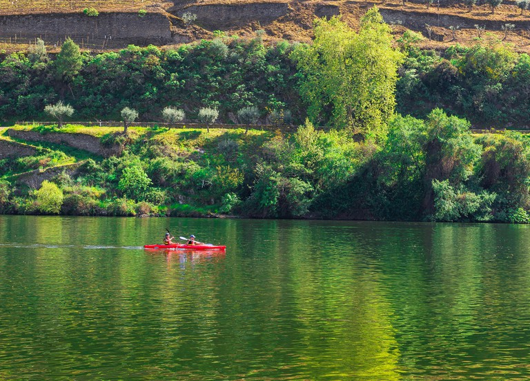 Portugal Douro Valley, a canoe carrying two people heads up the Douro River Valley near the port wine town of Pinhao, Portugal