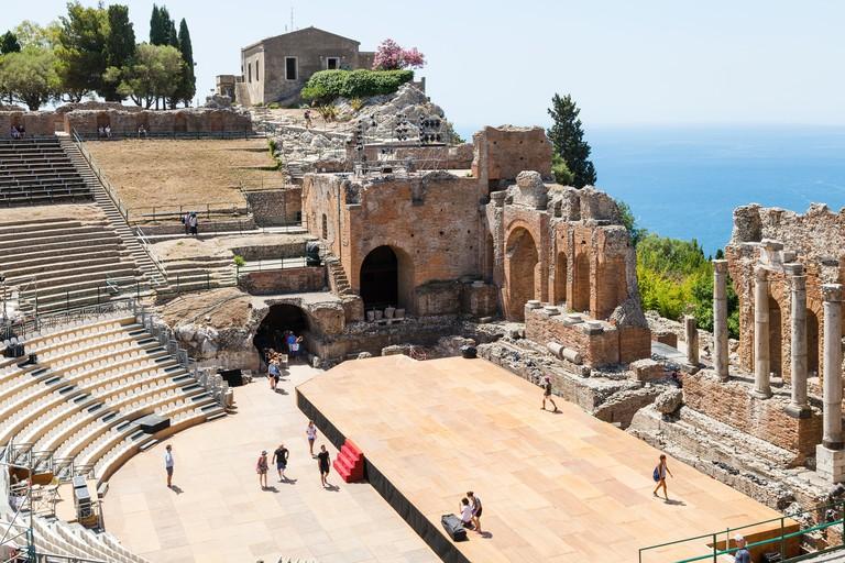 TAORMINA, ITALY - JUNE 29, 2017: visitors in Teatro antico di Taormina, ancient Greek Theater (Teatro Greco) in Taormina city in summer day. The amphi