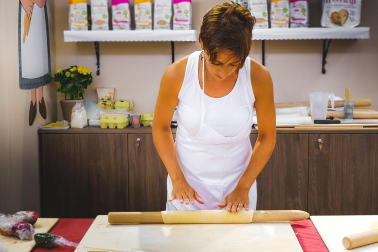 K7HBRK Bologna, Italy, 10 Sept 2017: Woman fare la sfoglia ( doing the pasta sfoglia) for fresh homemade pasta with rolling pin