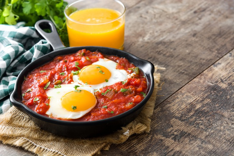 KGFRW8 Mexican breakfast: Huevos rancheros in iron frying pan on wooden table