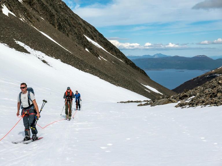 Backcountry alpine skiers climb on ski skins; roped for glacier crossings; Glaciar Martial; Mount Krund; Cerro Castor; near Ushuaia; Argentinanear Ush