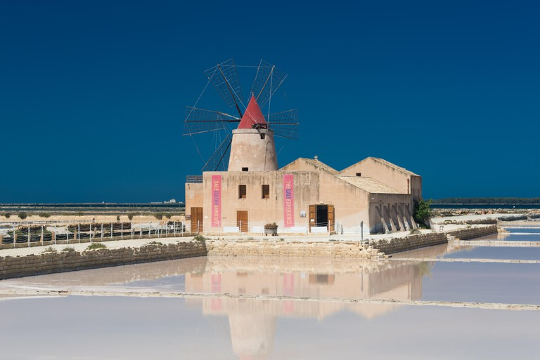 The salt museum with a windmill with reflection in the salt pans at the salina of Mozia at the west coast of Sicily between Trapani and Marsala.
