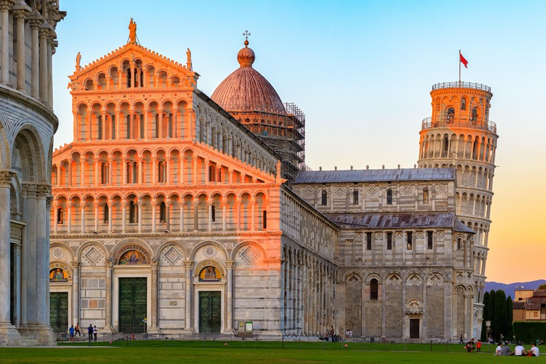Golden sunlight hit on the top of the Leaning Tower and Pisa Cathedral in Italy at sunset
