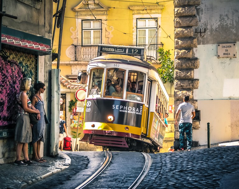Lisbon. Famous old tram climbing uphill in Alfama.