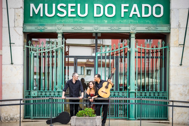 Portuguese guitar player, fado singer and acoustic guitar player in front of Fado Museum in Lisbon, Portugal
