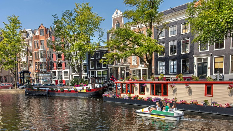 The Netherlands, Amsterdam. Prinsengracht canal. Houseboats and 17th century houses. Pedal boat. RBAFJP