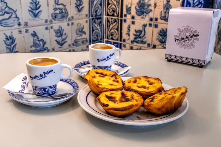 Pastel de belem or pasteis de nata custard tarts served with a cup of coffee at the historical Pasteis de Belem cafe in Belem, Lisbon, Portugal