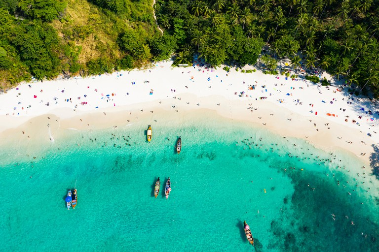 View from above, aerial view of a beautiful tropical beach with white sand,  turquoise water and long-tail boats, Freedom beach, Phuket, Thailand.