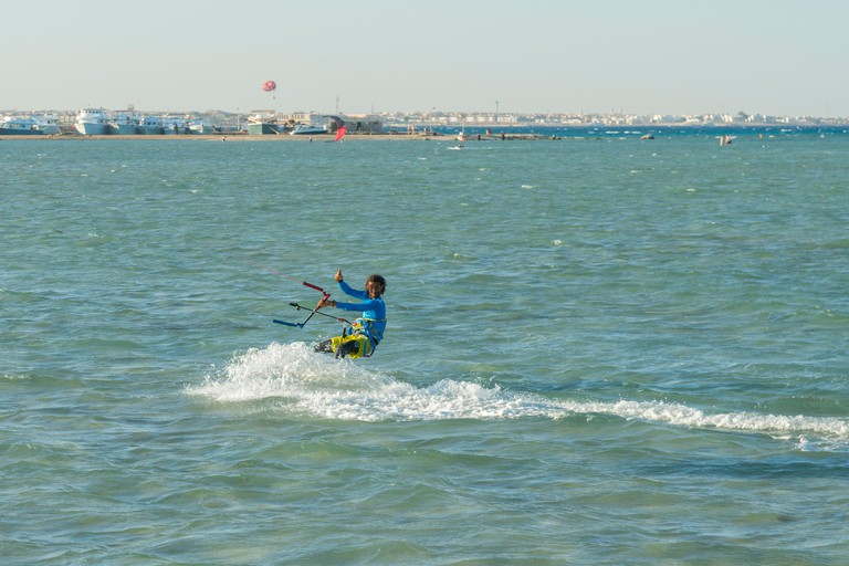 Hurghada, Egypt. November 19 2018 Kitesurfing Kiteboarding action photos man among waves quickly goes. A kite surfer rides the waves.