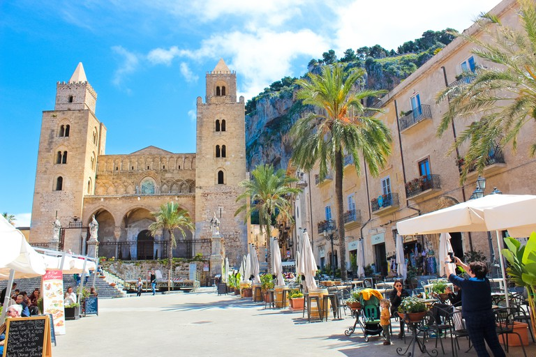 Cefalu, Sicily, Italy - Apr 7th 2019: Tourists on the old town square in the outdoor cafe gardens in front of Cefalu Cathedral. Famous Roman Catholic Basilica in Norman style is popular attraction.