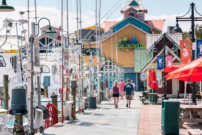 Destin, USA - April 24, 2018: Harborwalk village, people walking by marina with Margaritaville restaurant tropical bar cafe on summer sunny day in Flo
