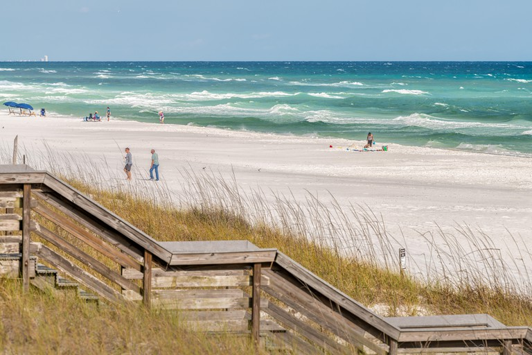 Destin, USA - April 24, 2018: Miramar beach city town in Florida panhandle gulf of mexico ocean water, wooden steps boardwalk to sand dunes with peopl
