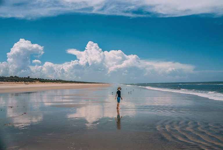 Person standing at New Smyrna Beach against cloudy sky