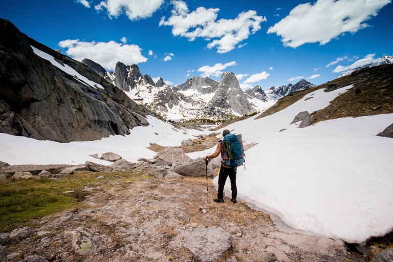 Hiker with backpack looking at view while standing at Grand Teton National Park