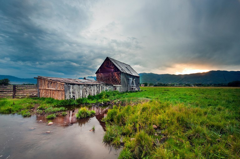 Menacing storm clouds frame an old barn at sunset in Midway, Utah. (c) 2013 Tom Kelly
