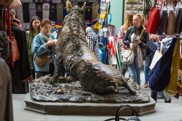 FLORENCE, ITALY - MAY 11, 2019: Fontana del Porcellino, a bronze boar rubbed by thousands of hands for luck. Tuscany, Italy
