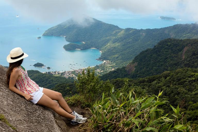Young woman looking out over the Green Coast (Costa Verde) from Papapagaio peak (Pico do Papagaio) on Ilha Grande island, Rio de Janeiro state, Brazil