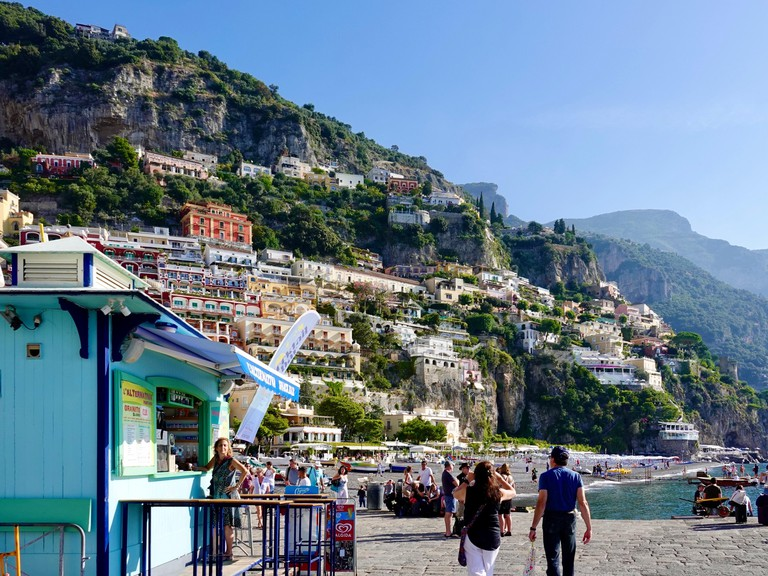 Woman standing in front of beverage kiosk while others relax on the broad Amalfi Coast expanse of beach in the hillside town of Positano, Italy.