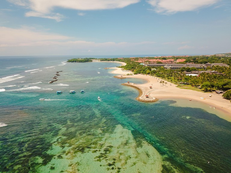 Aerial view of Nusa Dua Beach in Bali Indonesia with bay and a turquoise sea taken above from the sea during April with a drone
