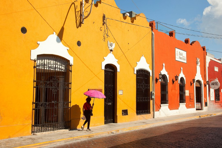 Woman walking in the street in front of the colonial buildings at the city center, Merida, Yucatan Province, Mexico, Central America