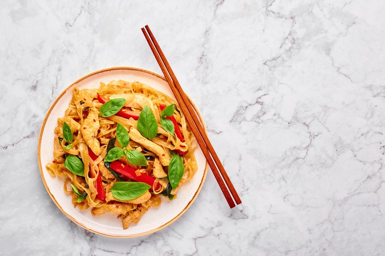 Thai Drunken Noodles or Pad Kee Mao at white marble background. Drunken Noodles is thai cuisine dish with Rice Noodles, Chicken meat, Basil, sauces an